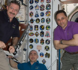 Expedition 30 commander Dan Burbank and Russian cosmonauts Anton Shkaplerov and Anatoly Ivanishin pose in the space station's Unity node.
