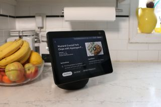 An Amazon Echo Show device on a kitchen counter with a bowl of fruit beside it