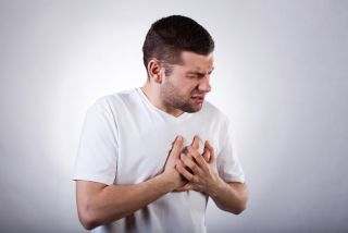 A young man clutches his chest in pain.