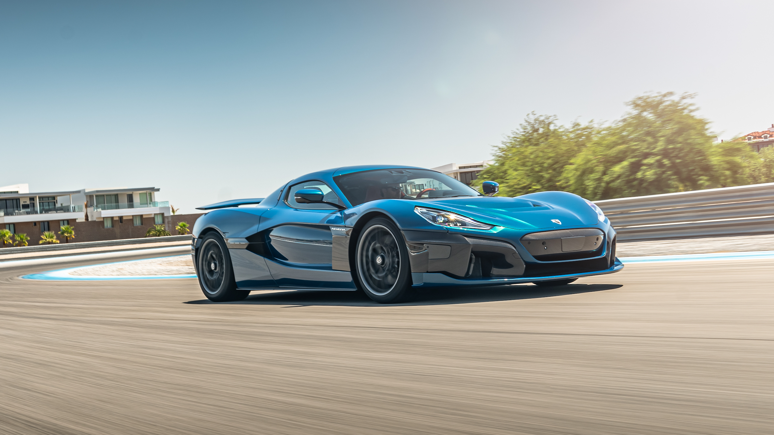 A Rimac Nevera driving on a road in summer