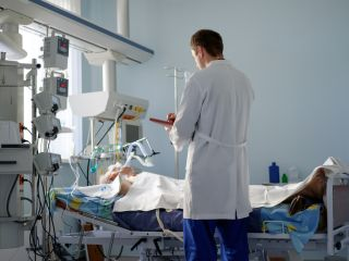 Doctor standing beside ICU patient in bed