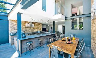Open-plan kitchen-diner in contemporary self build with high ceilings and exposed brick walls