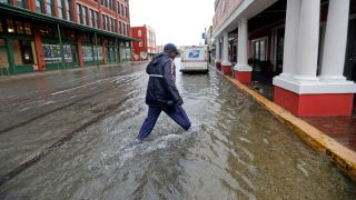 A postman walks through streets flooded by the tropical storm Imelda, as he delivers mail in Galveston, Texas.