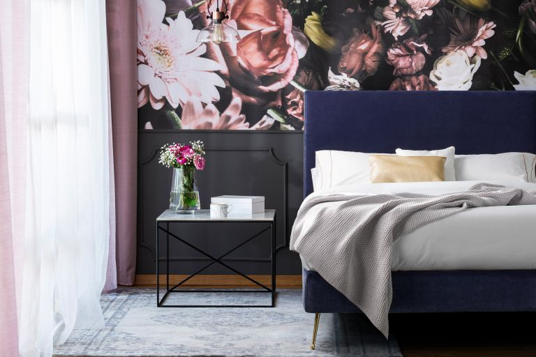 Floral mural in green bedroom with blue upholstered bed, grey throw and low pile rug