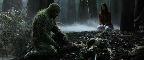 Swamp Thing and Abby Arcane look sadly over the skeleton of Alec Holland