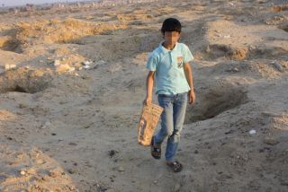 A child walks between looting pits dug at the ancient Egyptian site of Abusir el-Malek.