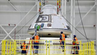Technicians observe as Boeing's Starliner crew module is placed on top of the service module in the Commercial Crew and Cargo Processing Facility at NASA's Kennedy Space Center in Florida, on Jan. 14, 2021. The Starliner spacecraft is being prepared for Boeing's second Orbital Flight Test (OFT-2).