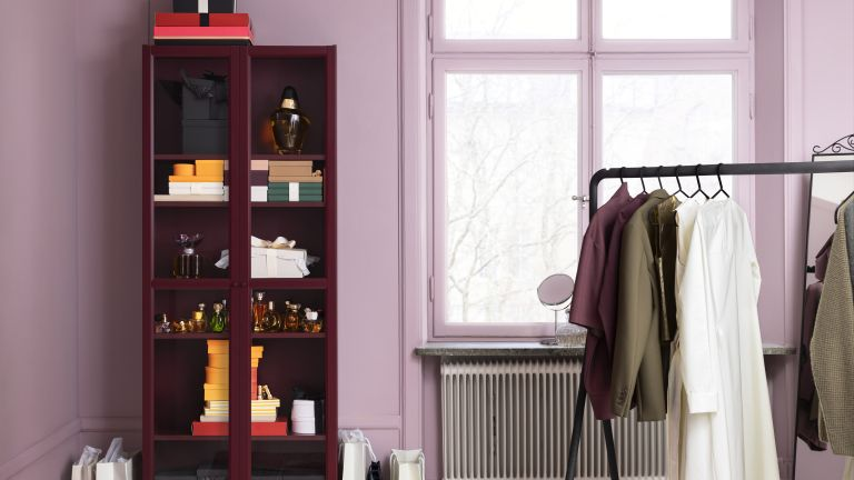 Dark painted IKEA cabinet in a pink bedroom with clothing rail