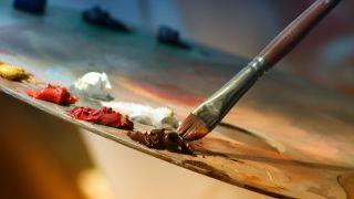 Paintbrush mixing paints on palette