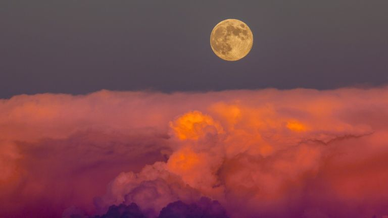Harvest moon on the Autumn equinox. The moonrise just after it rose above a bank of storm clouds in southwestern Colorado near Hovenweep National Monument.