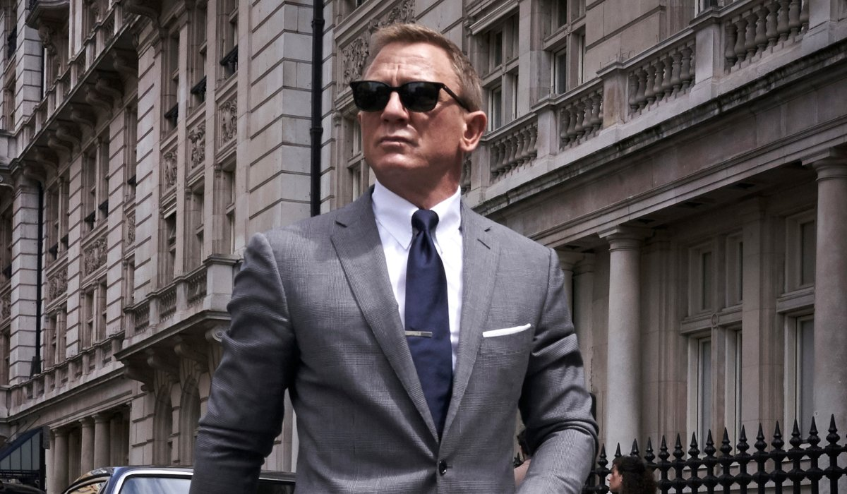 No Time To Die Daniel Craig walking in a grey suit and sunglasses