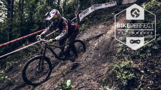 A downhiller rides a muddy track using the best MTB mud tires