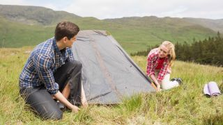 how to pitch a tent: couple setting up wild camp