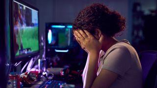 Upset gamer with her head in her hands