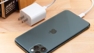 An iPhone 11 Pro plugged into a charging adapter