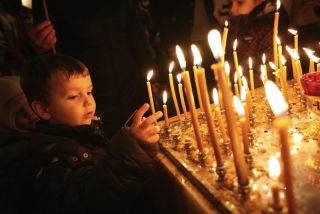 A child lights a candle in church.