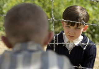 Asa Butterfield talks through a barbed wire fence to an out of focus Jack Scanlon