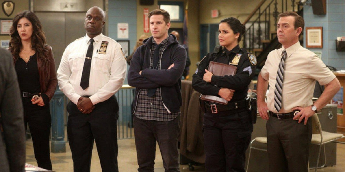 The cast of Brooklyn Nine-Nine working in their precinct.