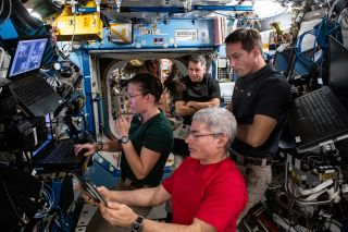 NASA astronauts Meghan McArthur (left), Shane Kimbrough (top center), Mark Vande Hei (bottom) and French astronaut Thomas Pesquet of the European Space Agency review spacewalk preparations on June 10, 2021. The three Americans won't have a long weekend for Fourth of July 2021.