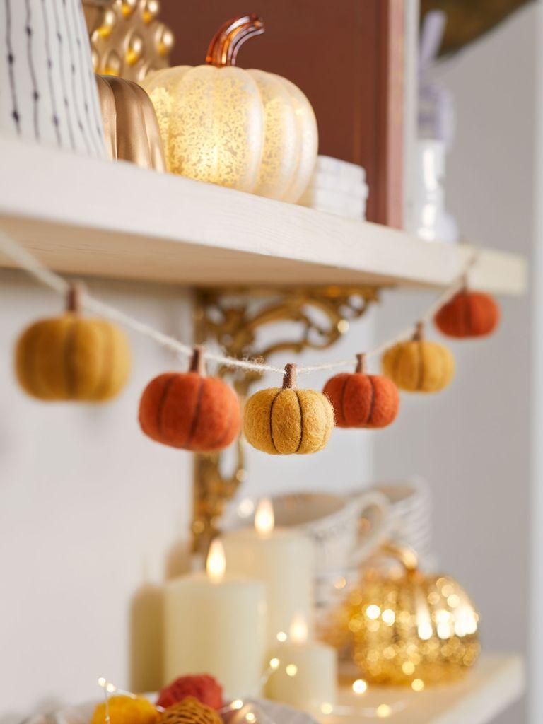 Felt pumpkin garland hanging from mantlepiece