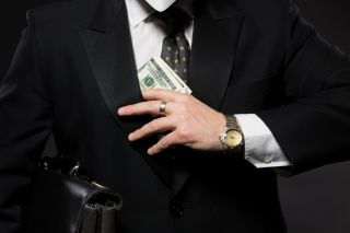 Businessman slipping money beneath suit jacket on dark gray background.