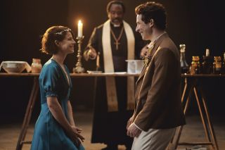 Juliet (Jessie Buckley) and Romeo (Josh O'Connor) smile warmly at each other while the Friar (Lucian Msamati) officiates their wedding.