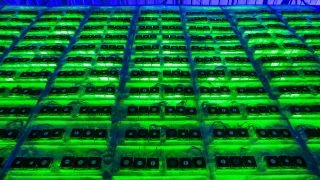 Illuminated mining rigs operate inside racks at the CryptoUniverse cryptocurrency mining farm in Nadvoitsy, Russia, on Thursday, March 18, 2021.