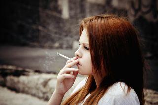 A teenage girl smokes a cigarette.