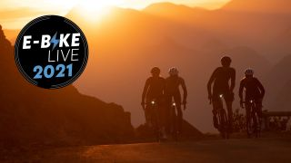 Four cyclists on electric bikes ride up a hill with a sunset behind