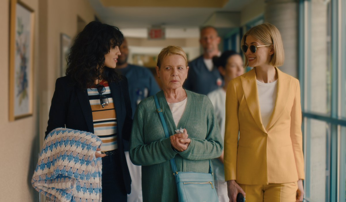 I Care A Lot Eiza Gonzalez and Rosamund Pike smile while flanking Dianne Wiest