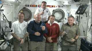 "Space shuttle commander Mark Kelly shows his ""Peace, Love, Gabby"" blue rubber bracelet, which he wears to honor his wife, wounded Congresswoman Gabrielle Giffords. Kelly, in blue, is floating in the International Space Station with his fellow NASA astrona"