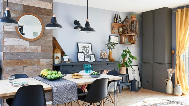 Spillett house: dining-living area with wood effect floor, wood dining table with metal pin legs, black Eames-style chairs, grey built-in storage and black pendants