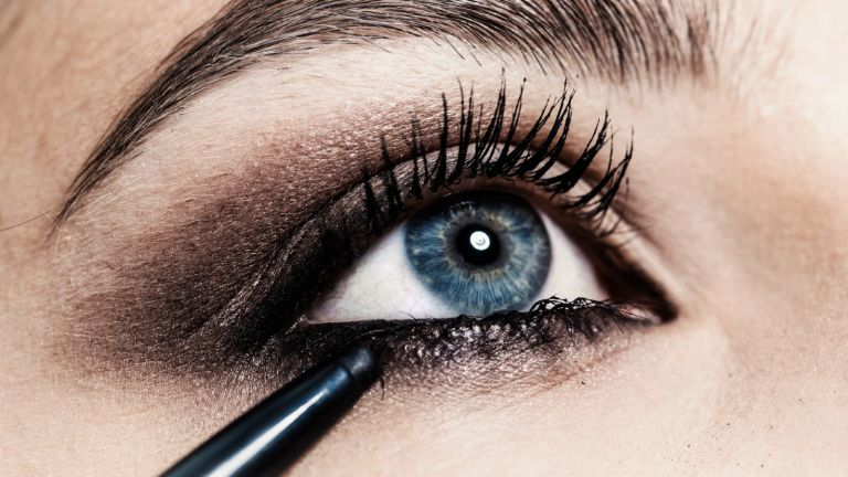 Close up of eyeliner being applied to young womans eye - stock photo