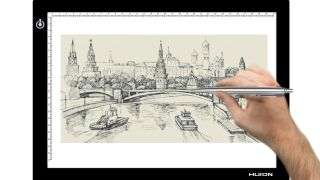 Hand tracing city scene onto paper using light pad