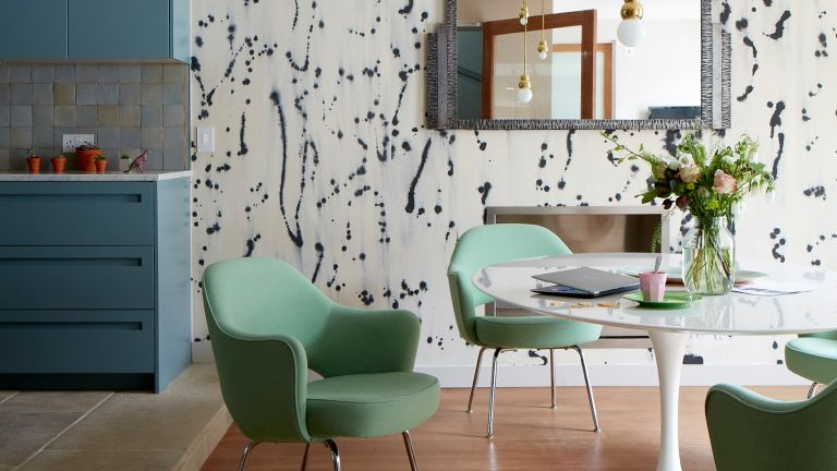 Open plan kitchen with dining area with blue wallpaper and green chairs