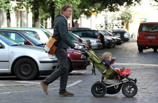 Oliver H., 42, a married federal employee on 6-month paternity leave, pushes his twin 14-month-old daughters Lotte and Alma in a pram while doing errands near his home on August 31, 2010 in Berlin, Germany.