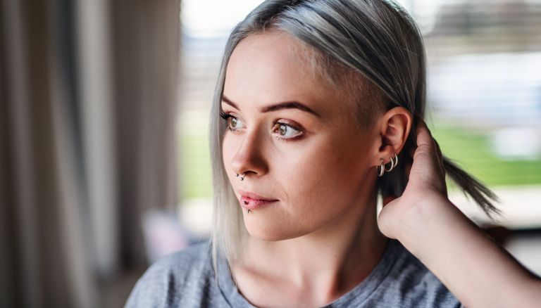 Front view portrait of young woman with multiple ear piercings at home