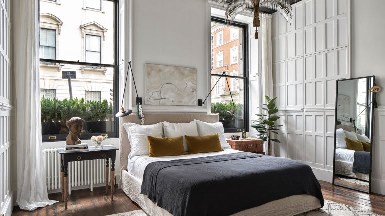 White bedroom with large windows and panelled walls