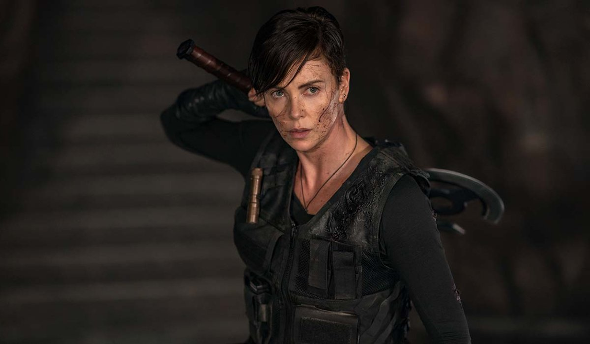The Old Guard Charlize Theron grabs a weapon from behind her back