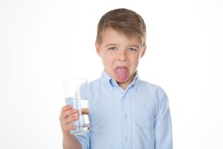 A little boy holds up a glass of water that tastes bad.