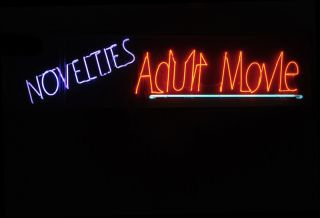 Neon adult video sign at night.