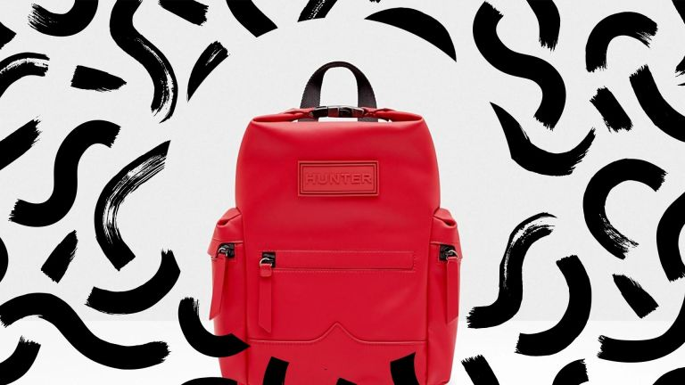 One of the best backpacks for working women: a Hunter rubberised leather backpack in red on a white background with black abstract swirls around it