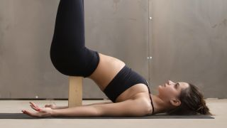 Woman doing yoga and balancing her back on a yoga block