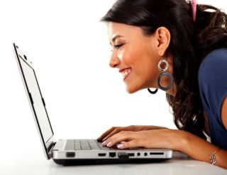 A woman looks at her laptop and smiles