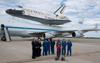 NASA Deputy Administrator Lori Garver, at podium, speaks to those in attendance at Apron W after the 747 Shuttle Carrier Aircraft (SCA) with space shuttle Discovery mounted on top rolled to a halt at Washington Dulles International Airport, Tuesday, April