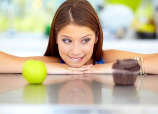 A woman decides between eating an apple or a cupcake