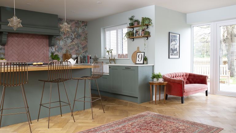 Open plan shaker kitchen with green units, brass bar stools and pink sofa