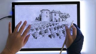 Best lightbox for tracing: Woman's hands tracing a picture using lightbox