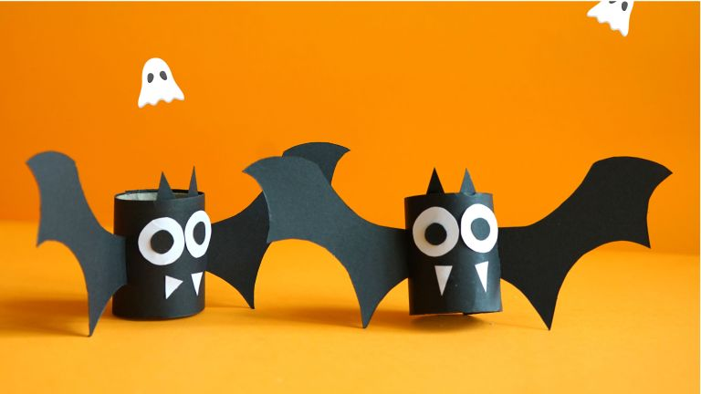 halloween craft ideas: bats made from toilet role tube on an orange background