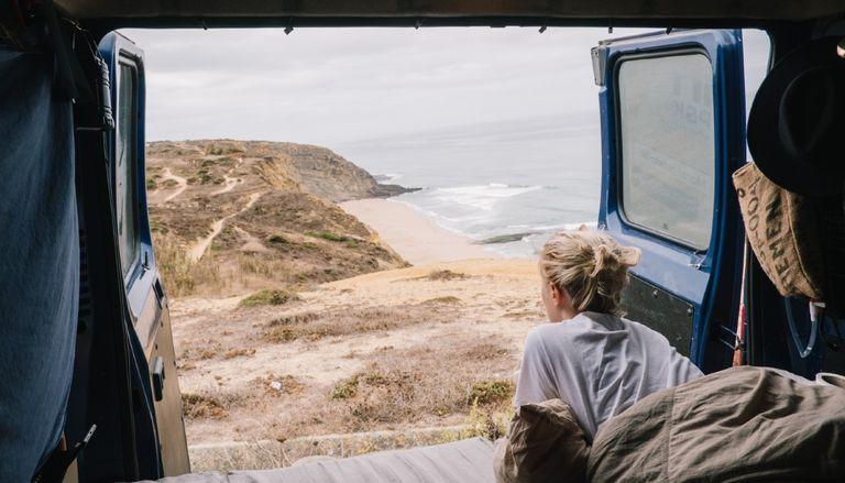 Person Sleeping In Van By Sea Against Sky, van life - stock photo